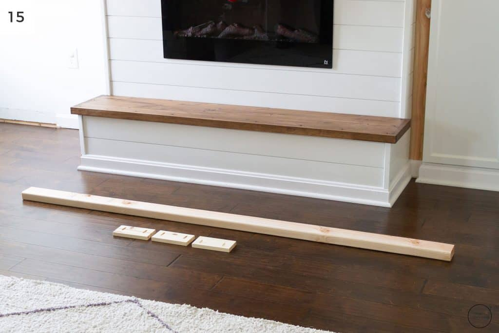 a wooden hearth below an electric fireplace with ship lap surround