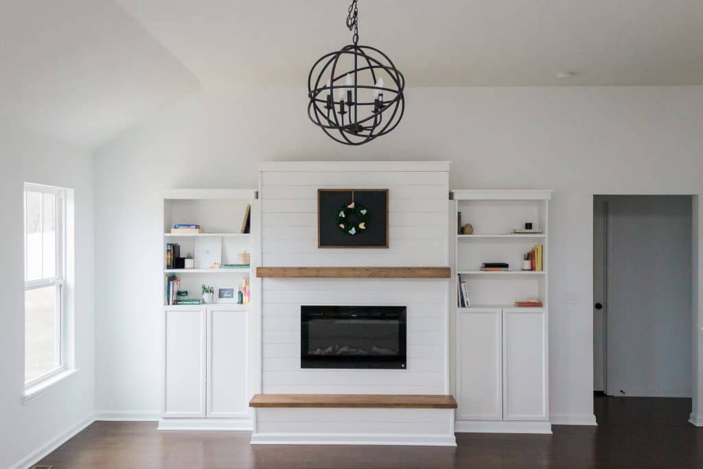A wooden framed chalkboard with butterfly wreath hung above an electric fireplace in a modern farmhouse-inspired great room