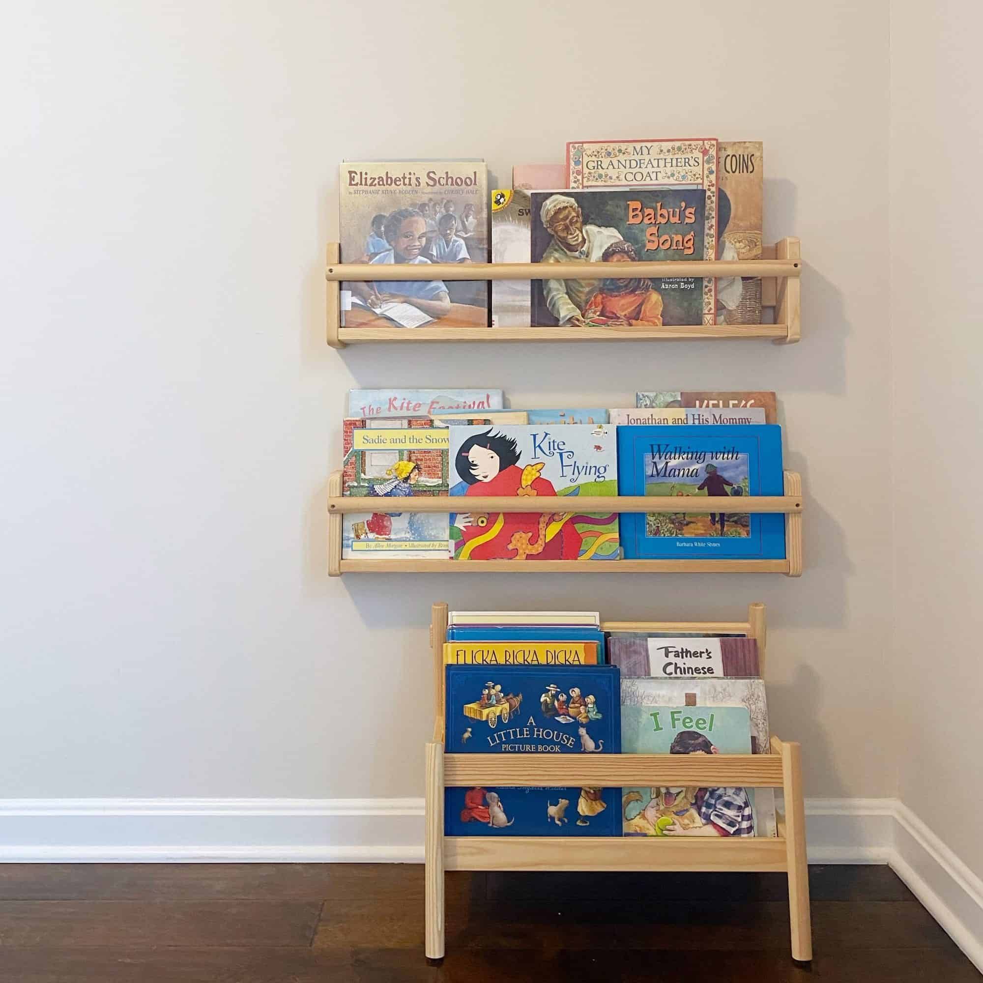 IKEA's FLISAT Wall Display Shelves and FLISAT Book Bin are used to create a small reading nook for children in a Montessori-inspired bedroom. #raisingreaders #earlyliteracy #booknook #montessori #montessoriathome #bookdisplay