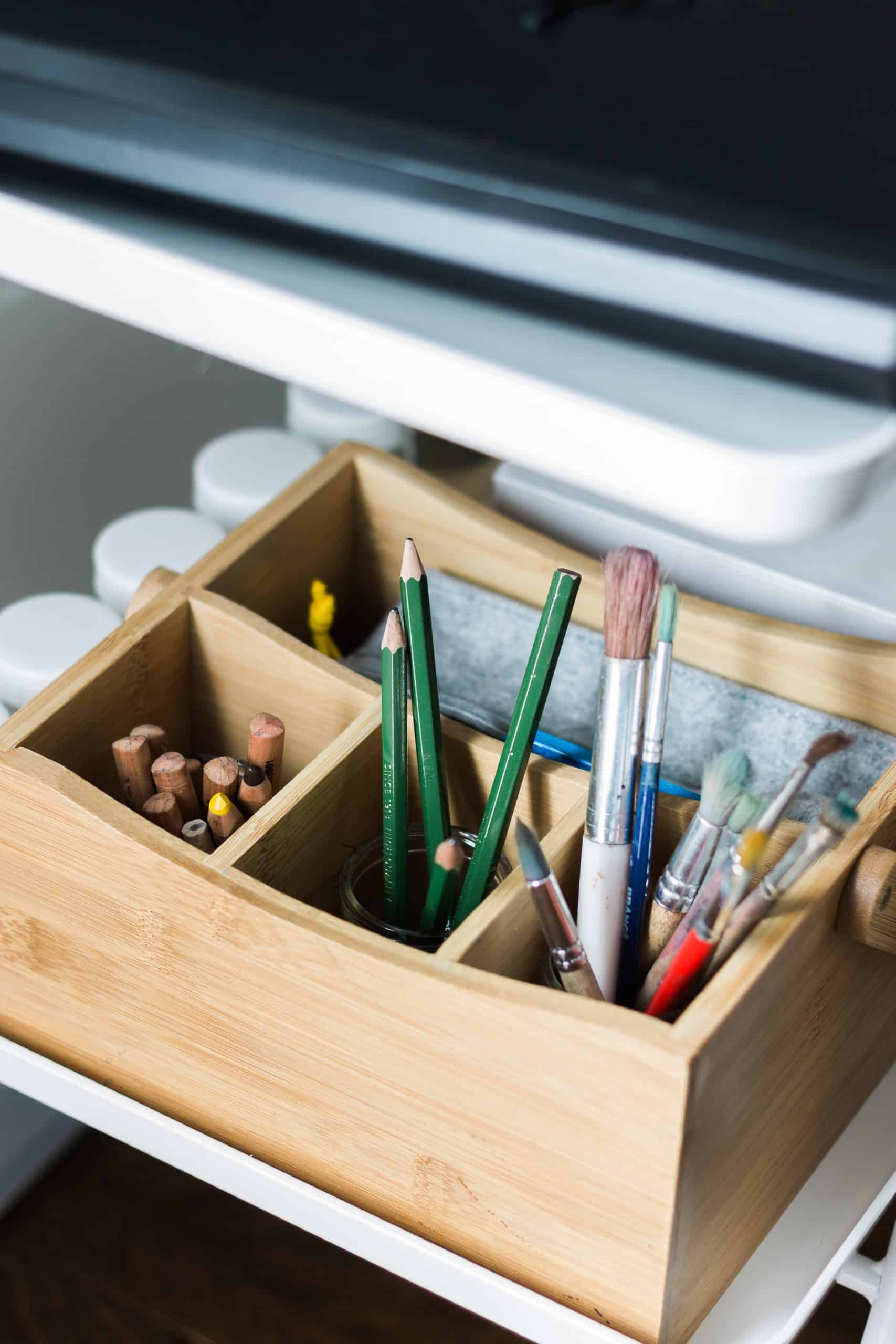 A bamboo storage caddy holds a variety of pencils, paintbrushes, and beeswax crayons along with other small bags to help keep art supplies and materials neatly organized.