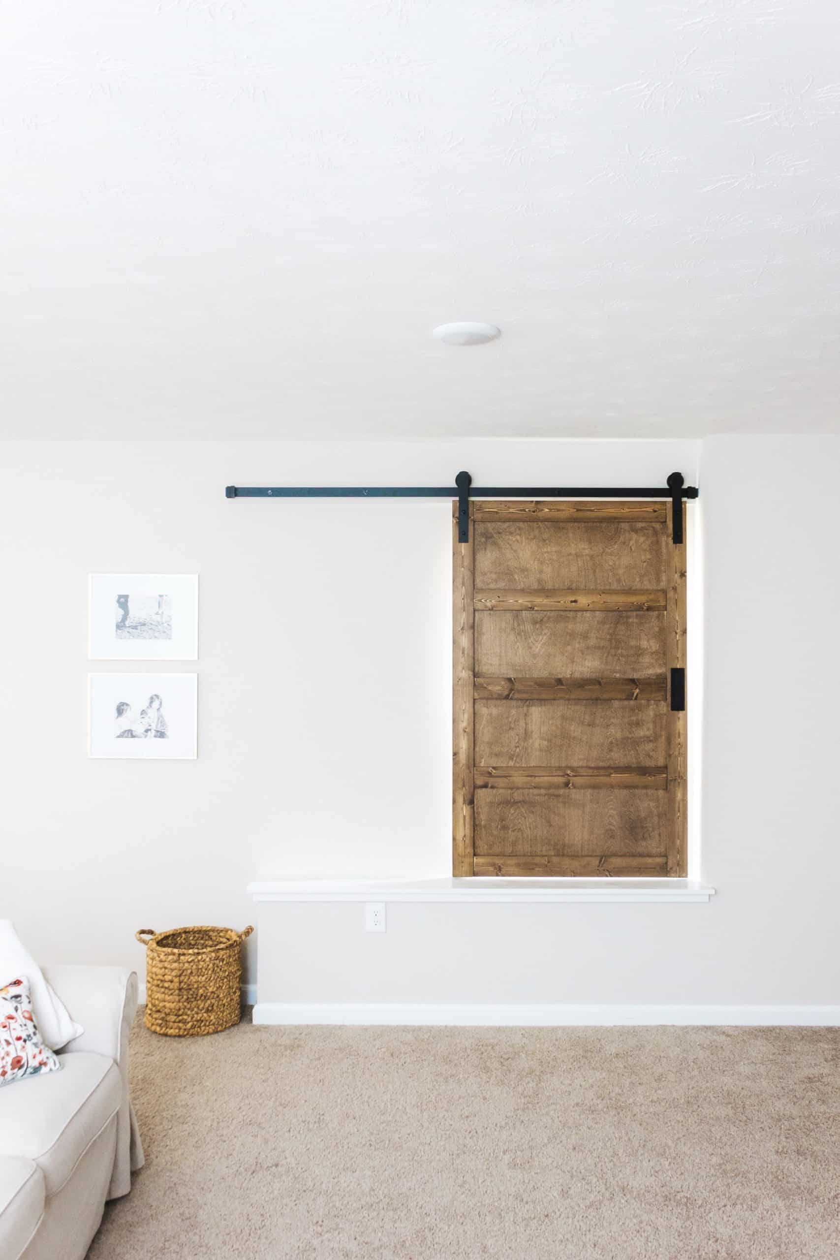 Want to build a modern farmhouse-inspired sliding barn door window covering? Head to www.freeandunfettered.com for the complete tutorial. #diyhome #modernfarmhouse #slidingbarndoor #diyhomedecor