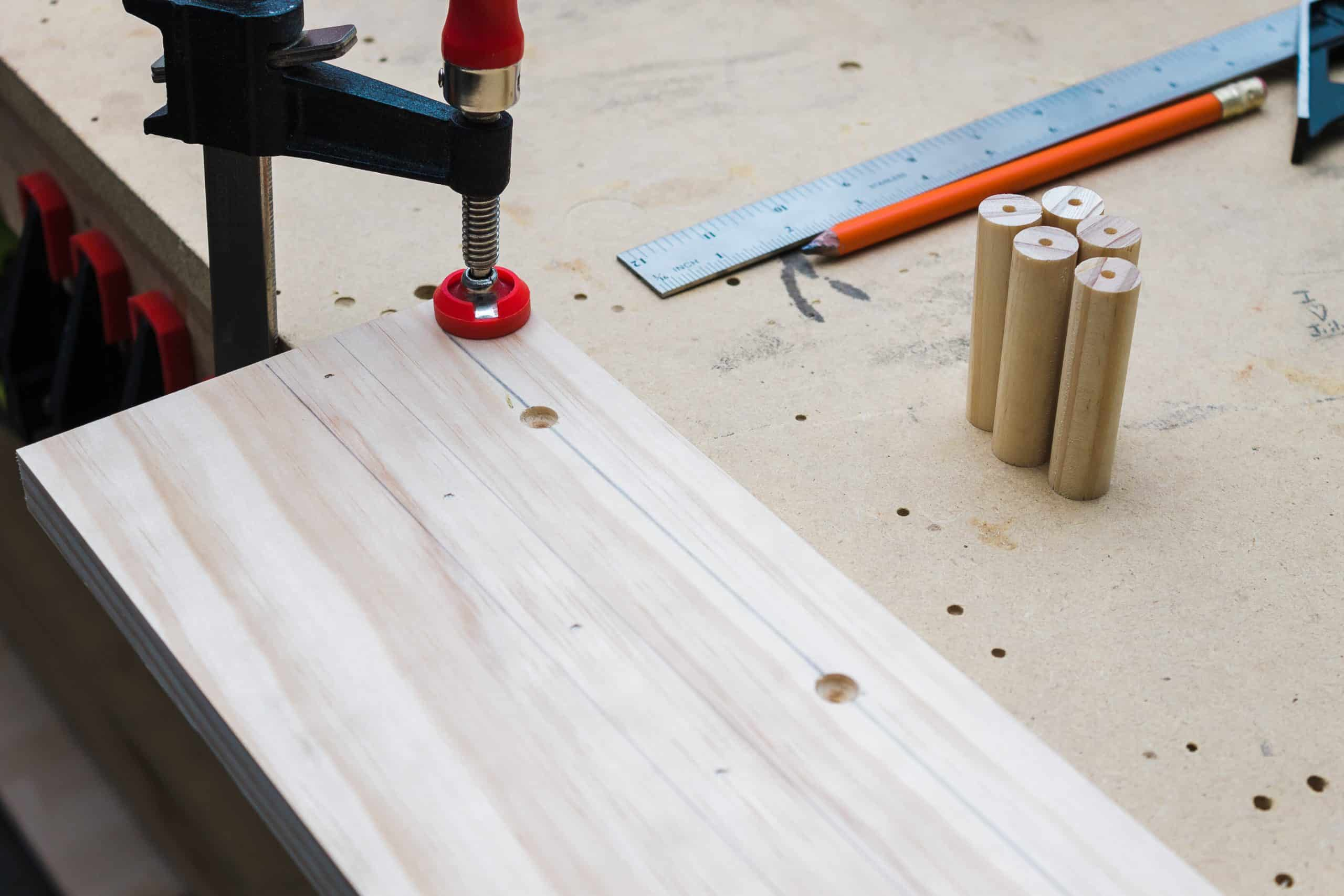 For an easier assembly, pre-drill center holes in each of the dowels for the DIY wooden peg rail shelf.