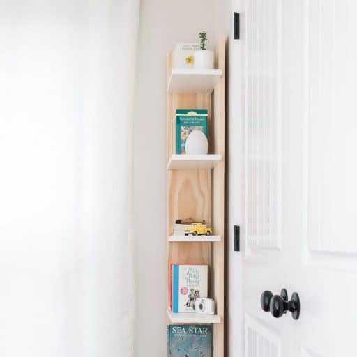 Learn how to build a narrow corner bookcase that's perfect for that awkward space behind a door. You can find the complete tutorial on how to build this for just $60 dollars by visiting www.freeandunfettered.com.