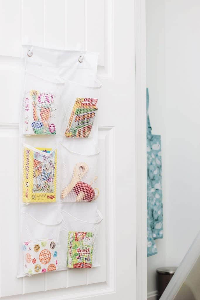 Card games are stored in pocket organizers hung on the back of the door with 3M Command hooks.
