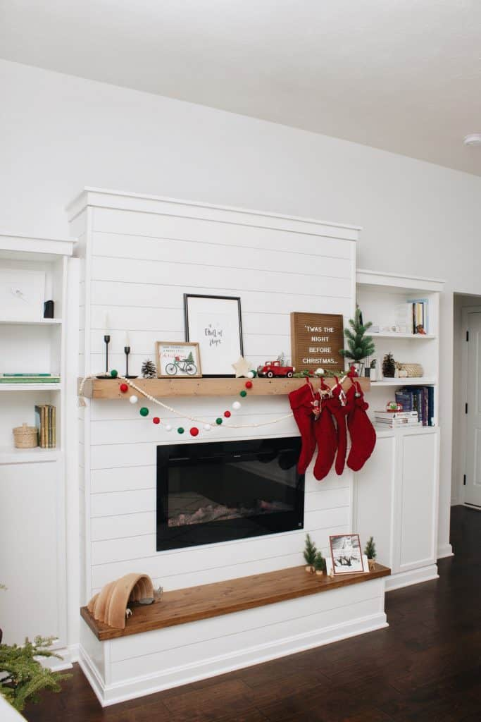 A side view of DIY shiplap electric fireplace build featuring a Touchstone Sideline electric fireplace and built-in Billy bookcases from IKEA.
