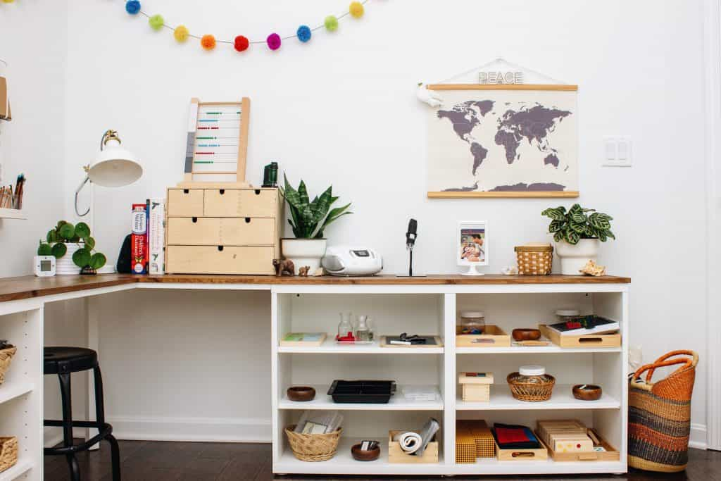 A detailed look at a Montessori homeschool room for both a primary and an elementary child, featuring a DIY corner desk using IKEA's BESTA units.