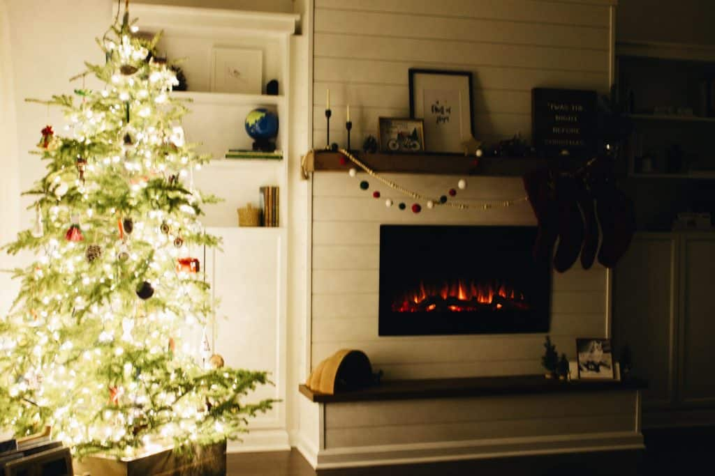 A step-by-step tutorial for how to build a shiplap electric fireplace insert wall -- a perfect project to make your home cozy for Christmas!