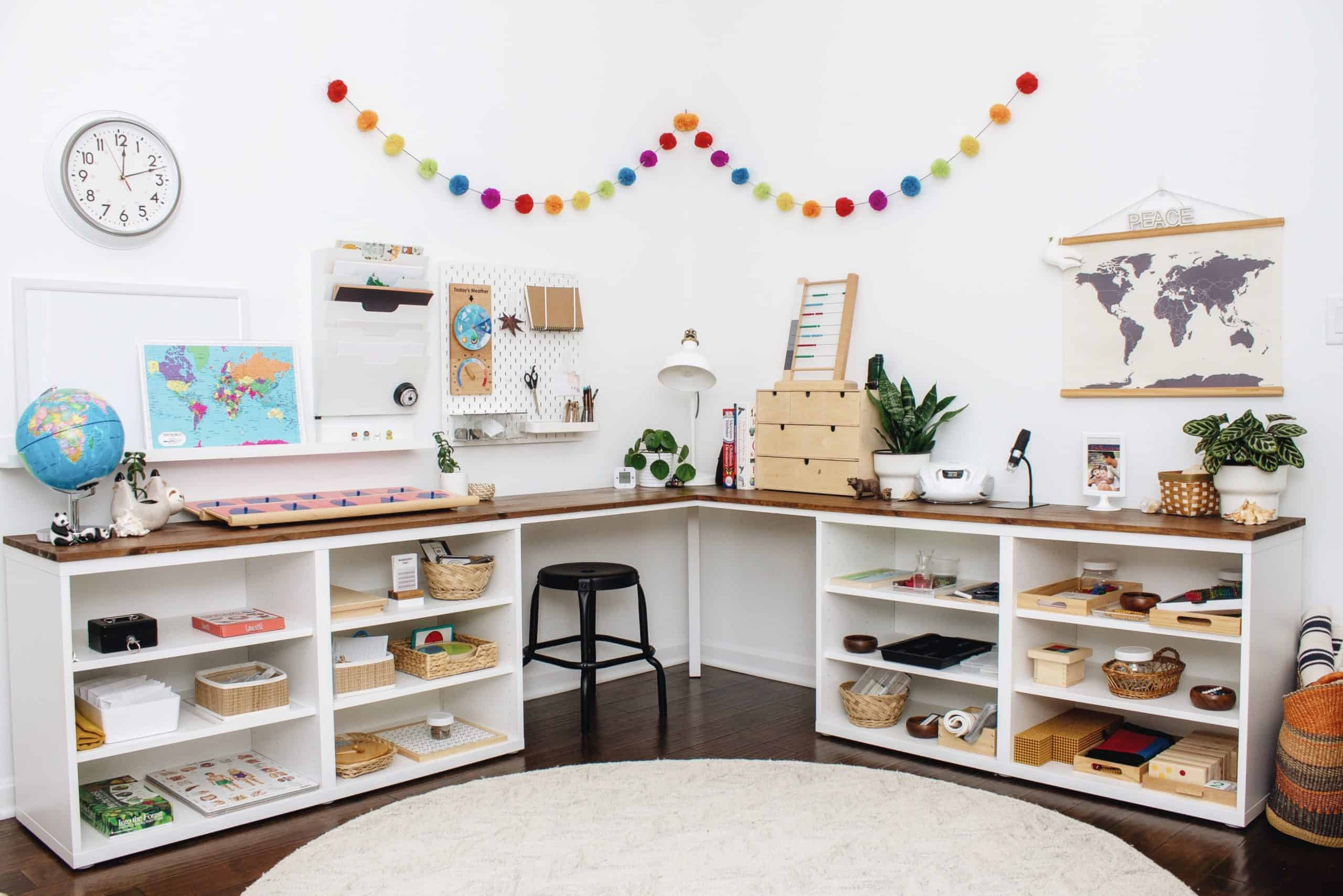 A Montessori homeschool room for both primary and elementary students with a DIY corner desk.