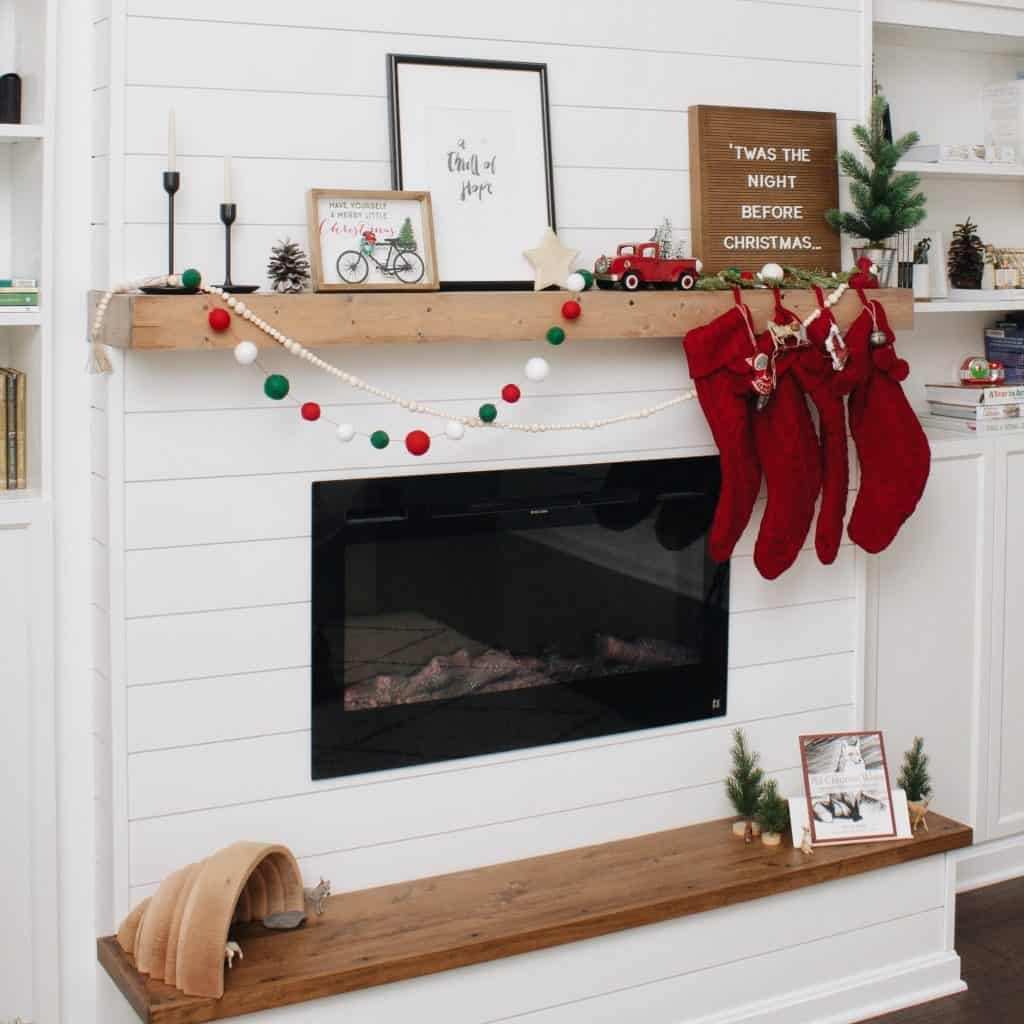 Christmas stockings hung on a DIY floating wooden fireplace mantel hanging above a Touchstone Products Sideline electric fireplace insert.
