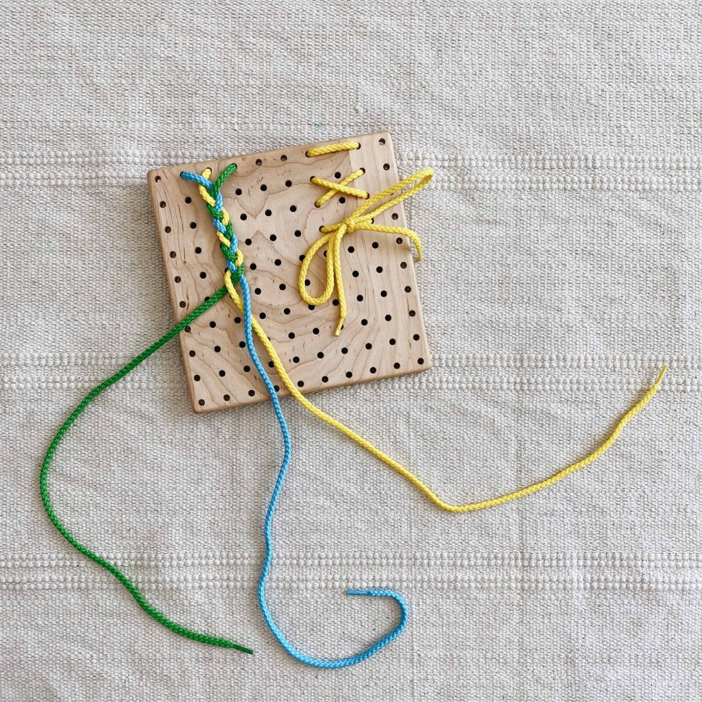 An embroidery board can also be used for a braiding and bow tying activity for preschoolers to help develop their fine motor and executive functioning skills.